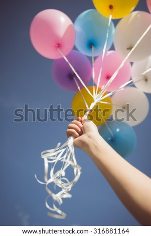 Vintage tone of person holding multi colored helium balloons. Focus at hand - stock photo