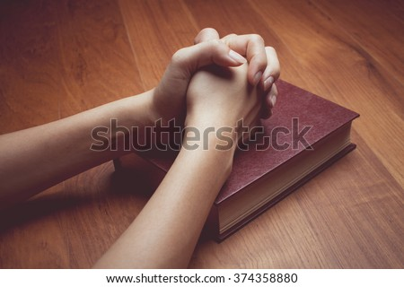 vintage tone of Woman hands praying with a bible - stock photo