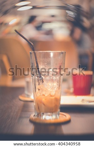 vintage tone photo effected  after drink delicious ice coffee in empty glass with swirly bokeh effectd from Petzval lens - stock photo