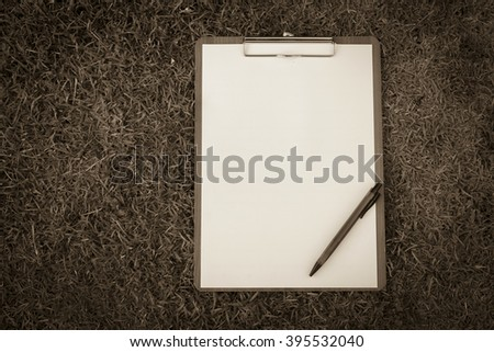 Vintage tone style blank paper on clipboard with grass background - stock photo