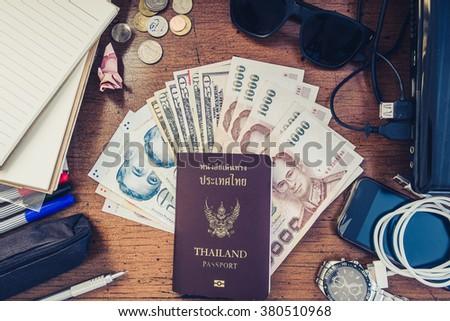 Vintage tone, travel preparation objects on desk, passport, cash, gadget and etc. - stock photo