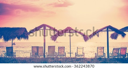 Vintage toned beach chairs and umbrellas at sunset, holidays background.  - stock photo