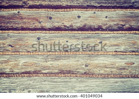 Vintage toned close up of a mountain cabin wooden wall, wood background. - stock photo