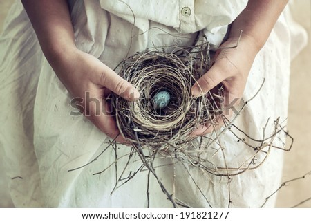 Vintage toned closeup of girl's hands holding a wild bird nest containing a blue and brown speckled egg. Soft romantic toning.