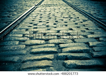 Vintage toned cobblestone street with old railroad track