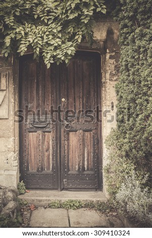 Vintage toned effect on wood door on stone building surrounded by greenery