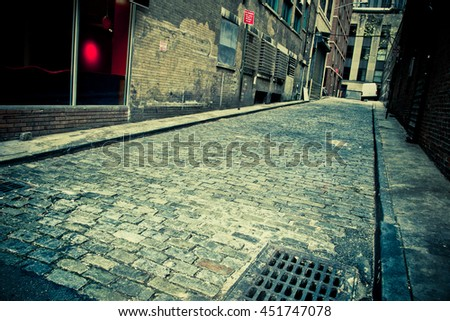 Vintage toned image of Old cobblestone alley in New York City with perspective   - stock photo