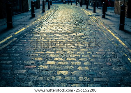 Vintage toned image of Old cobblestone road in London UK - stock photo