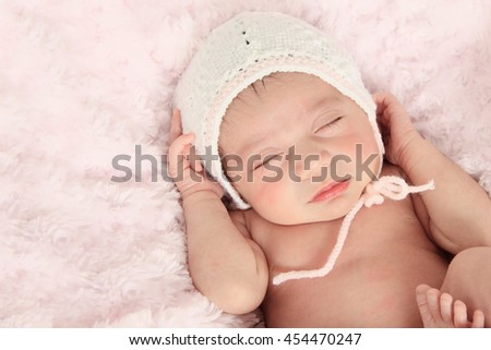 Vintage toned Newborn baby girl wearing a knitted bonnet.