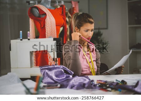 Vintage toned photo of a young woman designer sits in front of the sewing machine and looking at sketches of clothing.