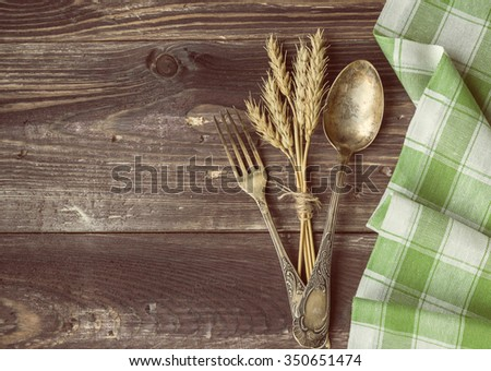 Vintage toned picture of the fork and spoon with the ears of wheat lying at the old table. - stock photo