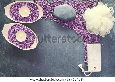 Vintage toned spa and wellness set with sponge, pumice stone and candles over slate background, copy space. - stock photo