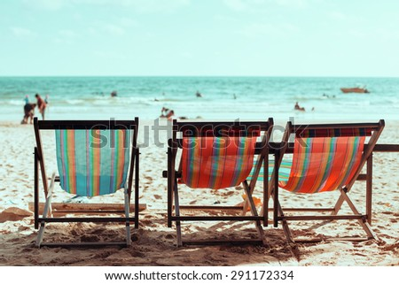 Vintage toned three beach chairs on tropical shore.