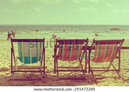 Vintage toned three beach chairs on tropical shore. - stock photo