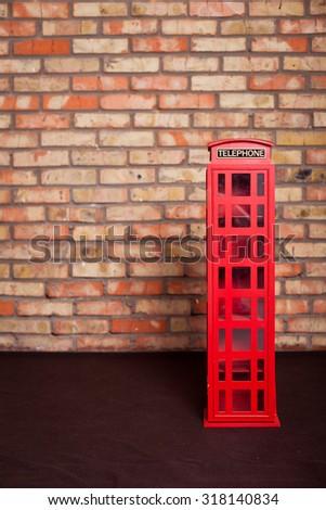 vintage toy phone booth near brick wall. Telephone box. Retro call box - stock photo