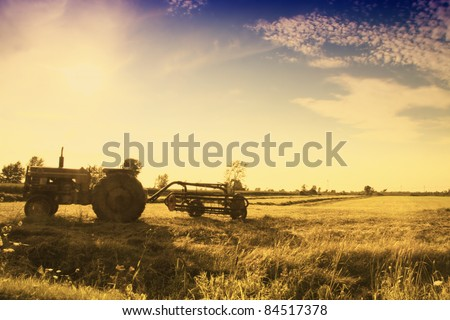 Vintage tractor in field left in the field at sunset - stock photo