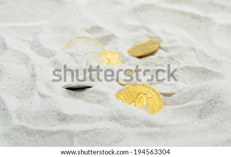Vintage treasure of gold coins in the sand. United States 19-20 age - stock photo