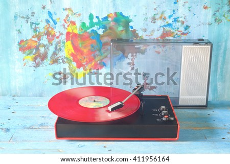 vintage turntable with red vinyl record and speaker - stock photo