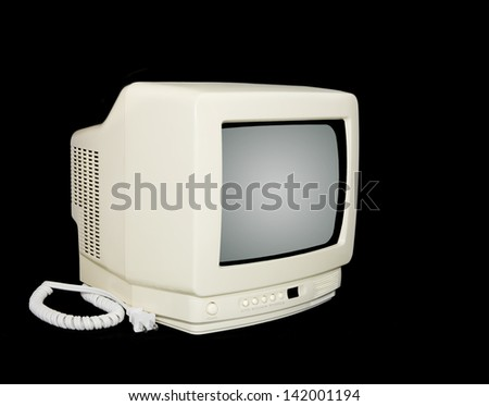 Vintage TV. A small television set from the 80's. Plastic off white enclosure with short white coiled power cord. Horizontal, isolated on a black background. Angled view. - stock photo