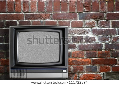 Vintage TV and brick wall - stock photo