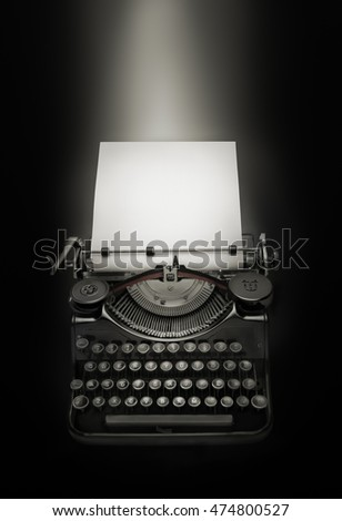 Vintage typewriter against black  background. Low key edition of an ancient typewriter integrated on black background.Space for text at the white page. Light effect over copy space