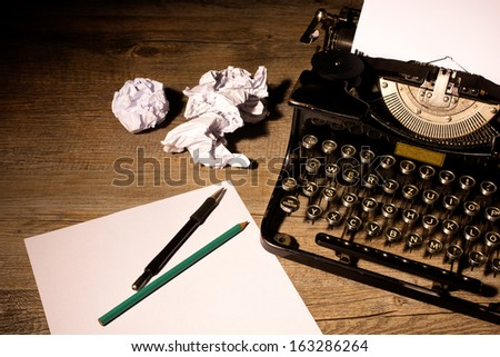 Vintage typewriter and a blank sheet of paper - stock photo