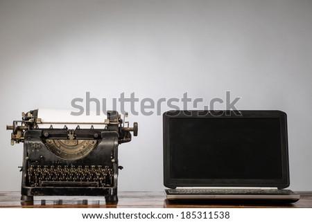 Vintage typewriter and laptop - stock photo