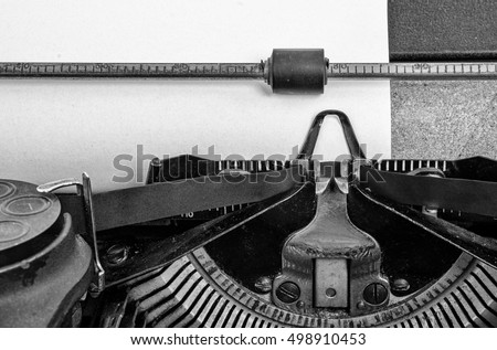Vintage typewriter. close up of blank paper on the platen ready for typing and printing onto. Black and white.