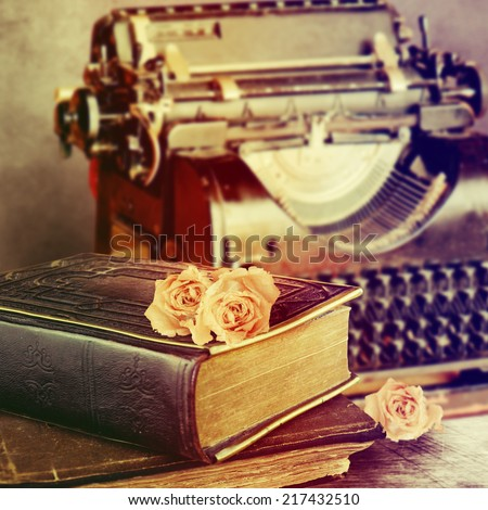 Vintage typewriter, old books on table. - stock photo