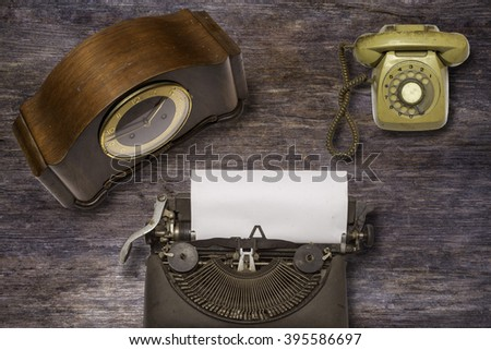 Vintage typewriter ,old clock  and old telephone on wood background