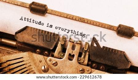 Vintage typewriter, old rusty, warm yellow filter, attitude is everything - stock photo