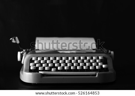Vintage typewriter on a black background. Creative writing concept. Writer. Close up of typewriter vintage retro styled. Typewriter with paper sheet. Space for your text.