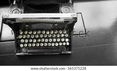 Vintage typewriter on black wood table.