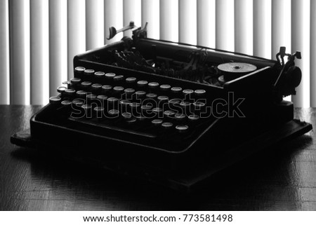 Vintage typewriter on the background of blinds. Black-and-white.