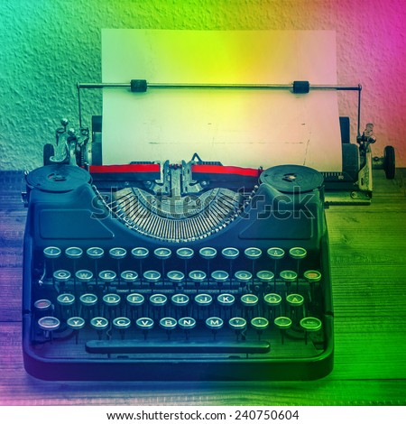 Vintage typewriter on wooden table with color spot lights. Grungy textured retro style colored picture. Creativity concept - stock photo