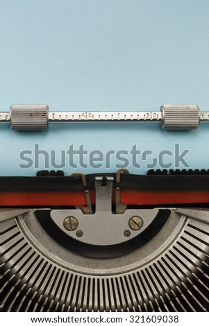 Vintage Typewriter With Empty Blue Paper Sheet Vertical Photograph - stock photo