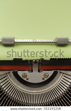 Vintage Typewriter With Empty Green Paper Sheet Vertical Photograph - stock photo