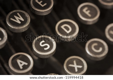 Vintage typewriter with grunge effects.  Shallow depth of field, black and white tones. - stock photo