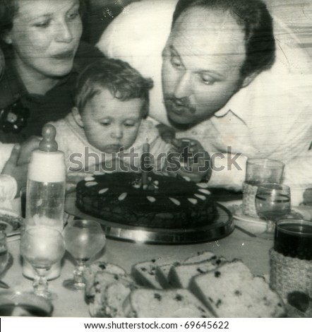 Vintage unretouched photo of parents and daughter (1st birthday) - stock photo