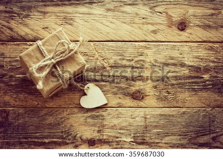 vintage valentine's day small gift box on old wooden table, retro sepia toned - stock photo