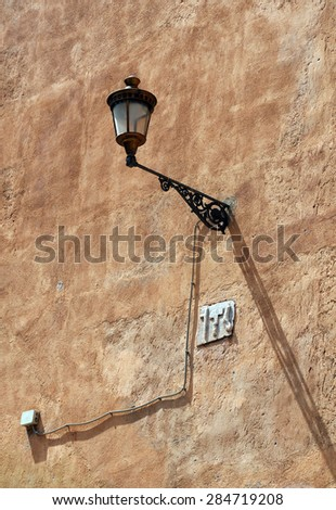 Vintage wall-mounted light on the rough wall of the building - stock photo