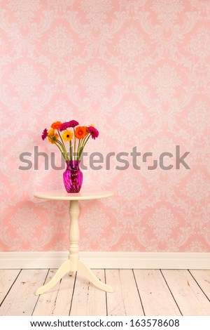 Vintage wall, wooden floor and plinth with white table and vase with flowers - stock photo