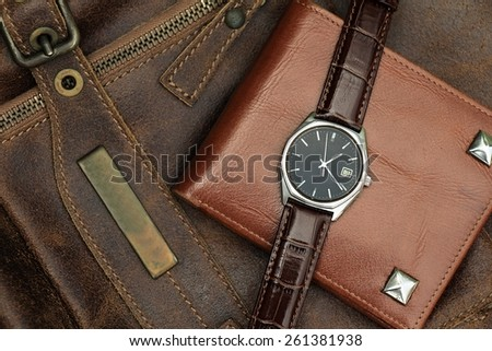 Vintage watch on a brown leather wallet. Classic Wristwatch. - stock photo