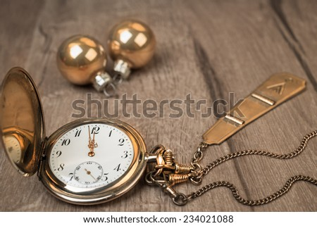 Vintage watch on a wooden background showing five to twelve - stock photo