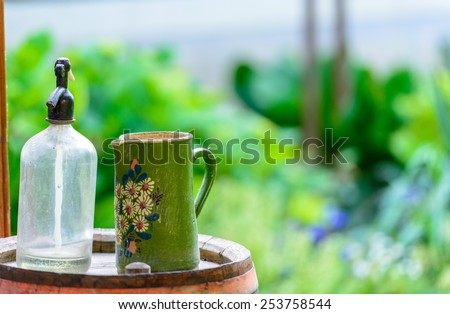 Vintage Water Siphon and Jug On a Barrel - stock photo