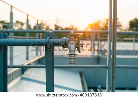 Vintage water tap or faucet at sunset - stock photo
