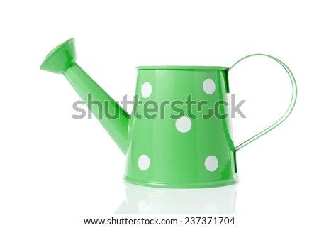 Vintage watering can with green color and polka dots isolated on white background. - stock photo