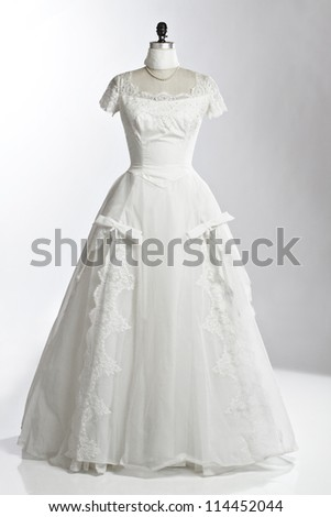 Vintage wedding dress of ivory tulle over satin with empire neckline, lace cap sleeves, princess waist, and fitted bodice. Displayed upright on stand. White background, vertical, copy space. - stock photo