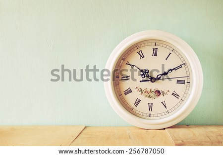 vintage white clock on wooden background - stock photo