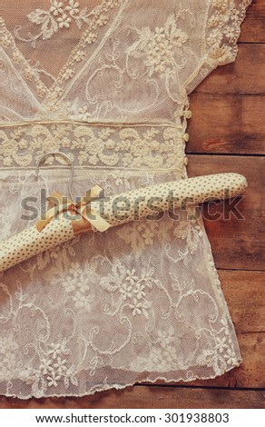 vintage white crochet lace top with romantic style fabric hanger on wooden background